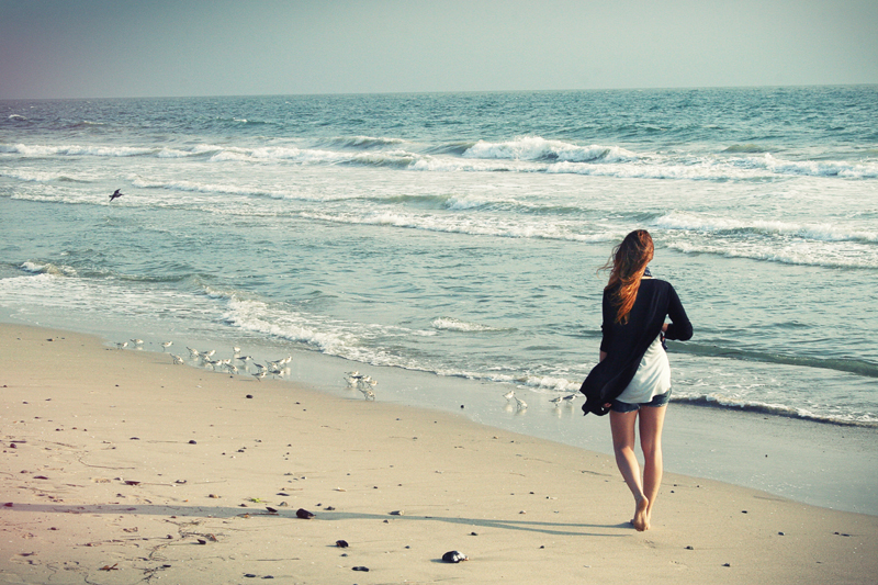 Woman walking on the beach in the morning