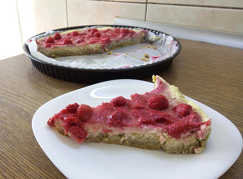 Slice of GF, SF, egg-free mango cheesecake with raspberry topping