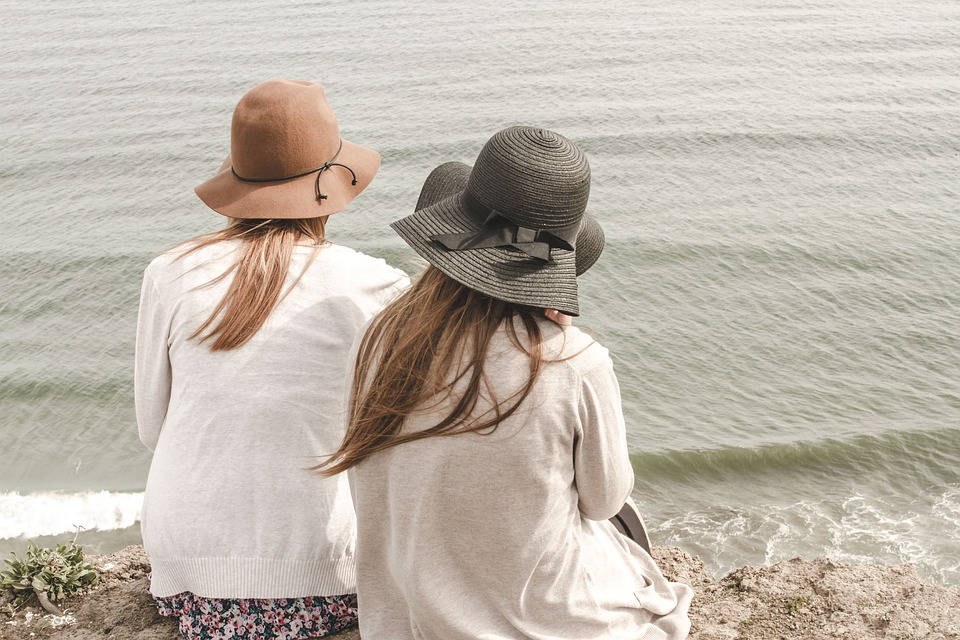 Women on the seashore sitting down on the sand, watching the sea together
