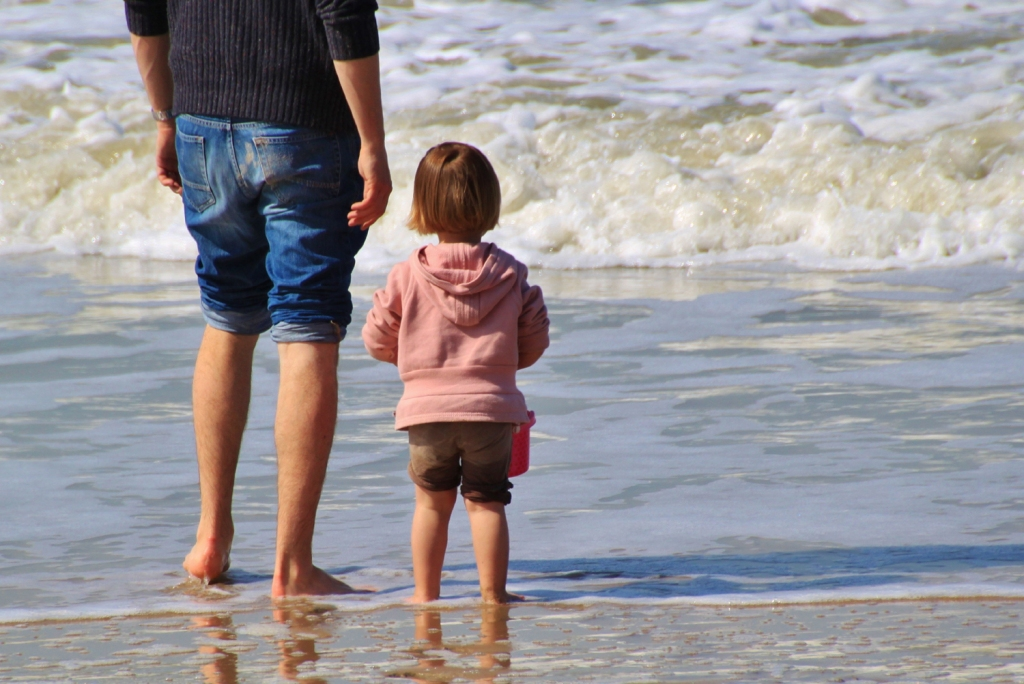 Father and daughter on the beach, at the edge of the sea, with feet in water (Father's Day wishes)