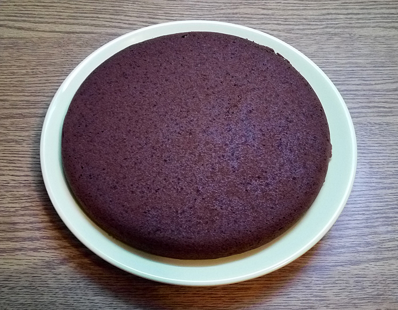 Cocoa cake layer, upside down on a plate