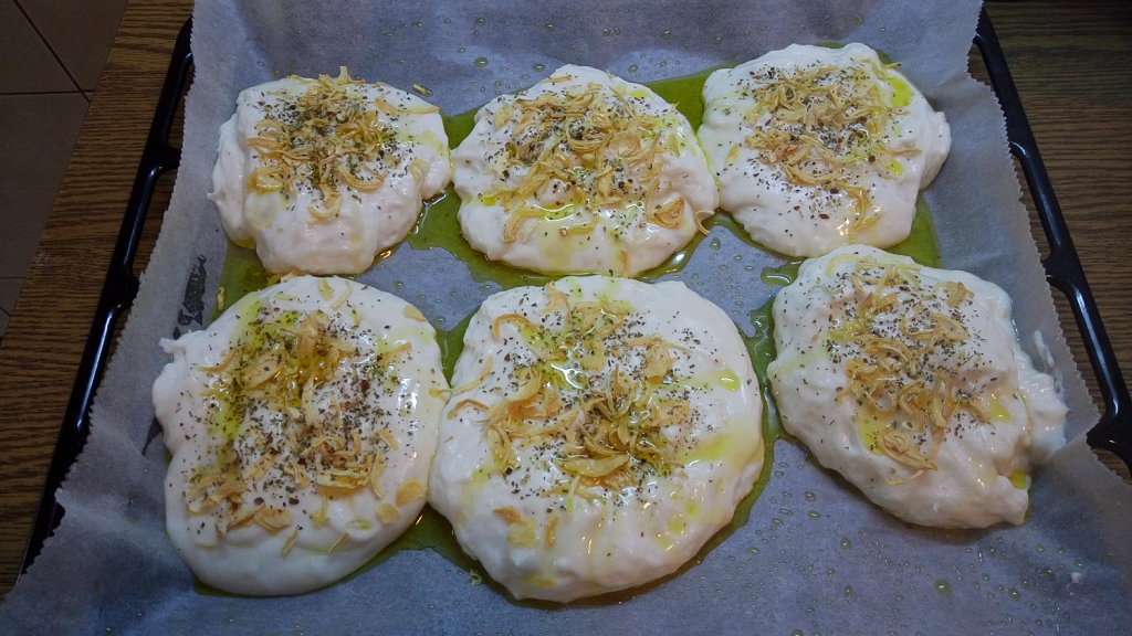 Balls of sticky dough, topped with onion flakes and spices, and with olive oil
