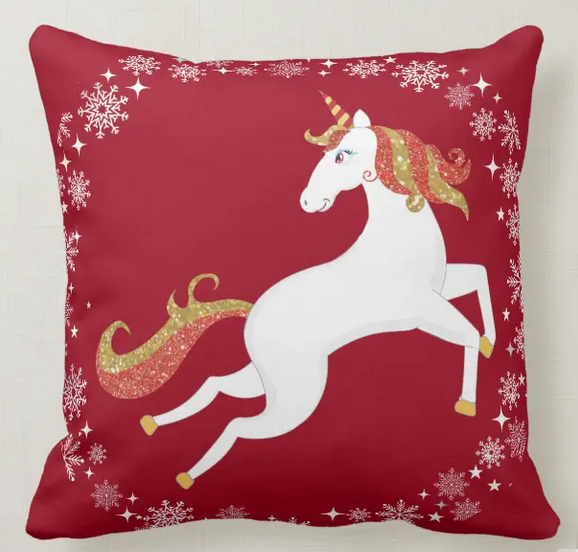 Christmas pillow with a magical unicorn with red and golden glitter in his mane and tail, and with a circle of snowflakes